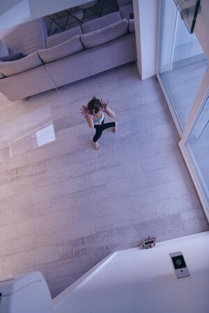 Little girl have online training over  tablet and doing modern ballet dance exercise at home. Online education concept class in modern ballet school. Social distance during quarantine, isolation in coronavirus top view