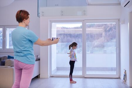 family at home little girl have online ballet training while mother is photographing her with smartphone
