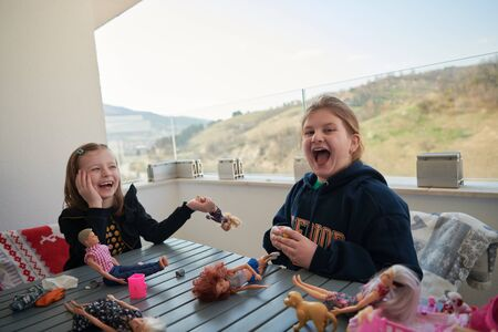 sisters or friends little girls playing with dolls on balcony