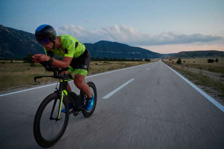 triathlon athlete riding professional racing bike at night workout on curvy country road w Banque d'images