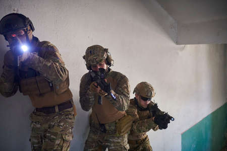 modern warfare soldiers ascent stairs in combat Stock Photo