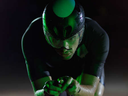 triathlon athlete riding bike at night Stockfoto