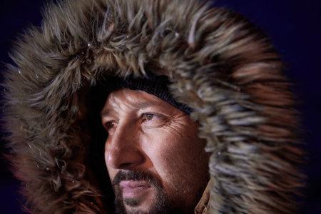 man at winter in stormy weather night wearing warm fur jacket Stock fotó