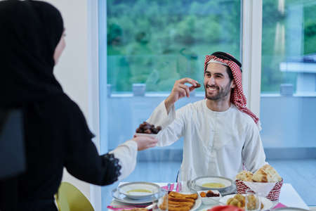 Muslim couple sharing dates for starting iftar