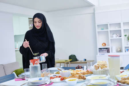 Young muslim woman serving food for iftar during Ramadan