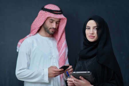 Young muslim business couple using technology devices