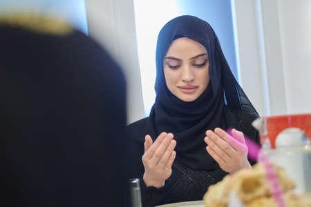 Muslim family making iftar dua to break fasting during Ramadan