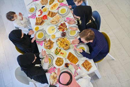 Top view of Muslim family making iftar dua to break fasting during Ramadan.