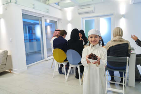Arabian kid in the traditional clothes during iftar