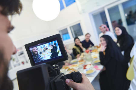Professional videograph recording video while Muslim family having iftar together during Ramadan