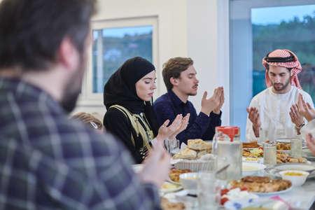 Muslim family making iftar dua to break fasting during Ramadan.