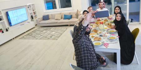 Muslim family taking selfie while having iftar together during Ramadan