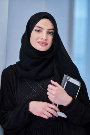 Young Arab businesswoman in traditional clothes or abaya with tablet computer Standard-Bild