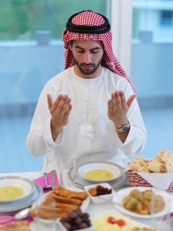 Muslim man making iftar dua to break fasting during Ramadan