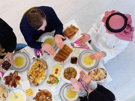 Top view of Muslim family making iftar dua to break fasting during Ramadan