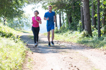 couple enjoying in a healthy lifestyle while jogging on a country road Stockfoto