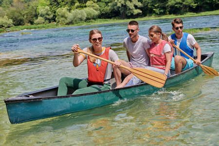 Group adventurous explorer friends are canoeing in a wild river