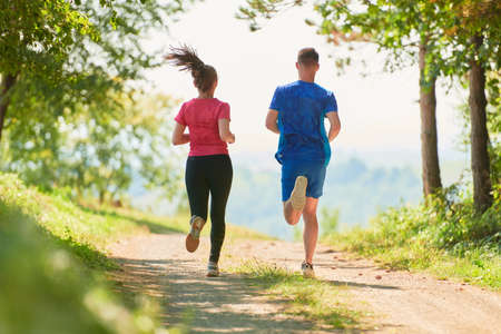 couple enjoying in a healthy lifestyle while jogging on a country road