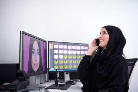 Muslim female graphic designer talking on the phone