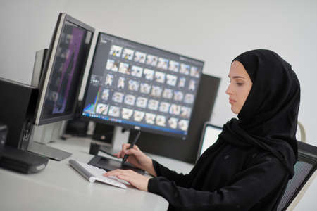 Muslim female graphic designer working on computer using graphic tablet and two monitors Stock Photo