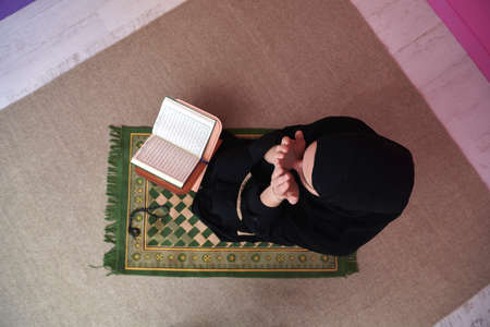 Middle eastern woman praying and reading the holy Quran Stock Photo