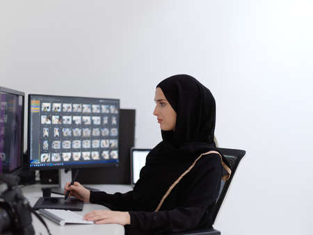 Muslim female graphic designer working on computer using graphic tablet and two monitors