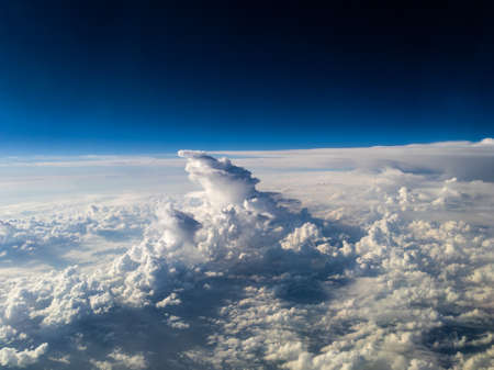 Aerial view of uniquely shaped white cumulonimbus clouds below on dark blue background