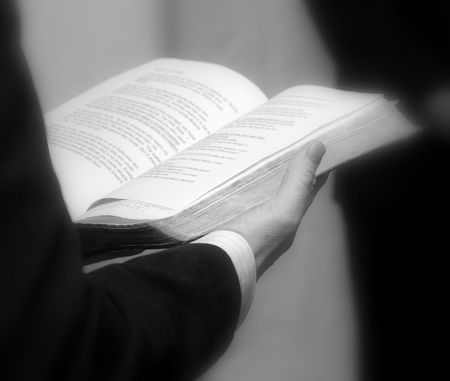Priest holding a bible. Close up in black and white