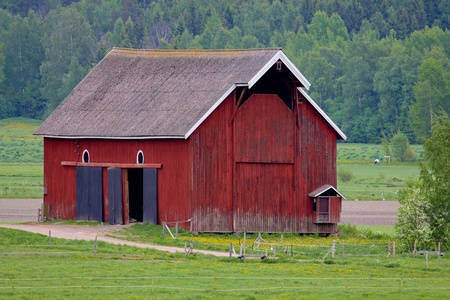 Old red barn. On a green field in Finlnad