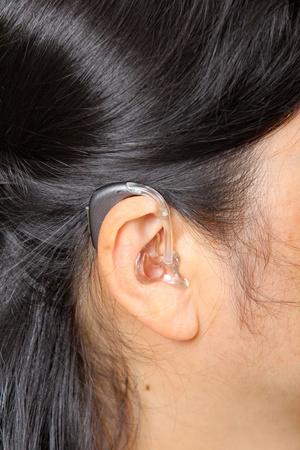 Hearing: Asian woman wearing hearing aid. Close up
