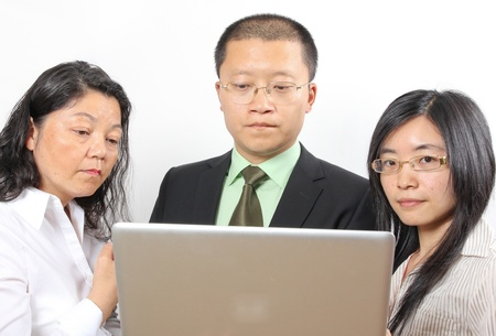 3 chinese businesspeople, standing around a table with a laptop computer photo