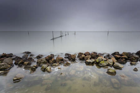 long lake: Lake Fishnets In Long Exposure With Moody Sky