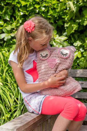 robo: Young Girl Holding Homemade Toy Crochet Owl In The Garden