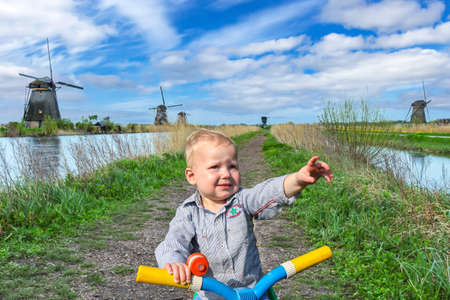 Little boy on his bike looking at the windmills at Kinderdijk, The Netherlands.
