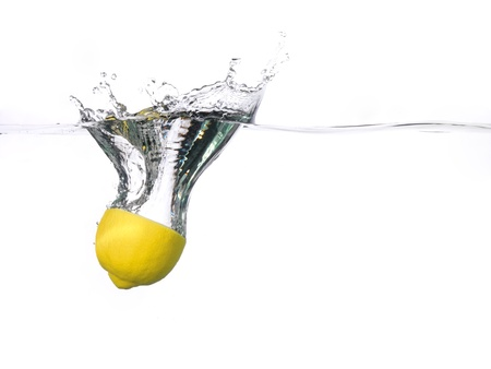 Lemon half falling into water, with a splash, white background