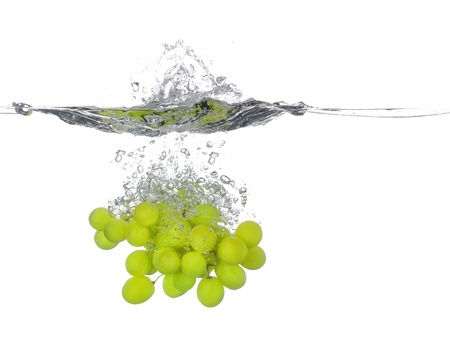 Bunch of green grapes falling into water, with a splash, white background