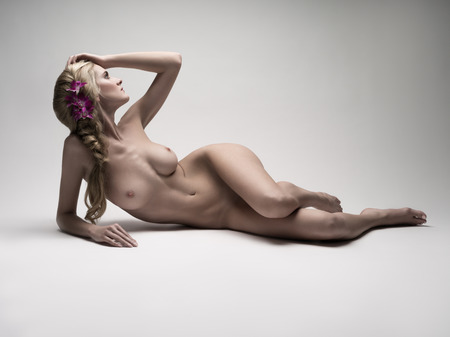 nude: Naked woman laying down on a white background Stock Photo