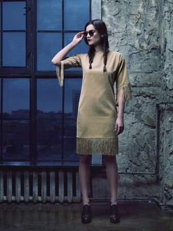 ankles sexy: Elegant fashion model wearing mustard dress, ankle boots and sunglasses, posing in front of the window Stock Photo