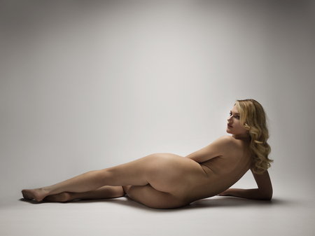 Naked woman laying down on a white background. Studio shot