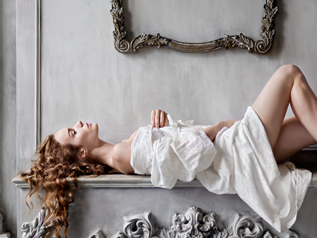 mantelpiece: Sexy young beautiful woman in a white baroque dress lying on the mantelpiece