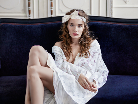 Perfect, sexy young woman wearing baroque white dress sitting on vintage sofa Stok Fotoğraf