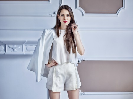 horozontal: Fashion portrait of a beautiful brunette woman in white blouse and shorts posing by a classic style wall. Stock Photo