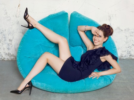 Young girl in a black dress lying on a blue sofa. Fashion style portrait.