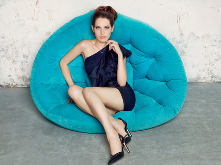 nude little girls: Young girl in a black dress sitting on a blue sofa. Fashion style portrait.