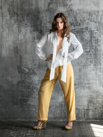 Studio portrait of stylish young woman in white shirt and yellow trousers Stock Photo