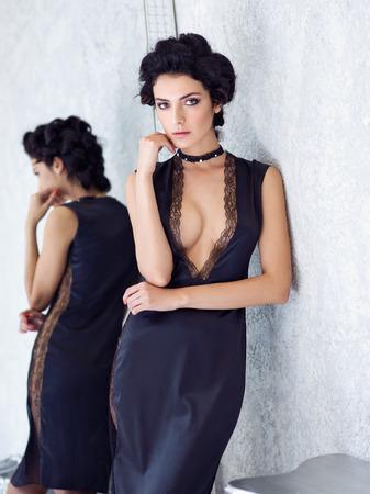 Beautiful brunette in black silk slip against mirror, Fashion style portrait. Imagens