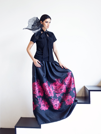 long skirt: Woman in black shirt and long skirt with floral print posing on stairs. Fashion style portrait