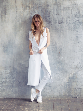 Full portrait of fashion woman wearing white design coat, trousers and sneakers. Fashion style shot