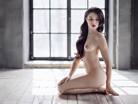 Young beautiful naked woman sitting on a floor