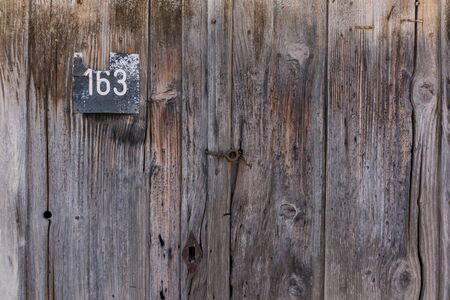 Old steel house number plate 163 on a wood background